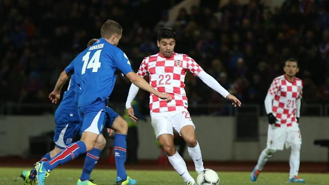 Iceland's Kari Arnason, left, challenges Croatia's Eduardo Alves da Silva for the ball during their World Cup qualifying playoff first leg soccer match in Reykjavik, Iceland, Friday Nov. 15, 2013