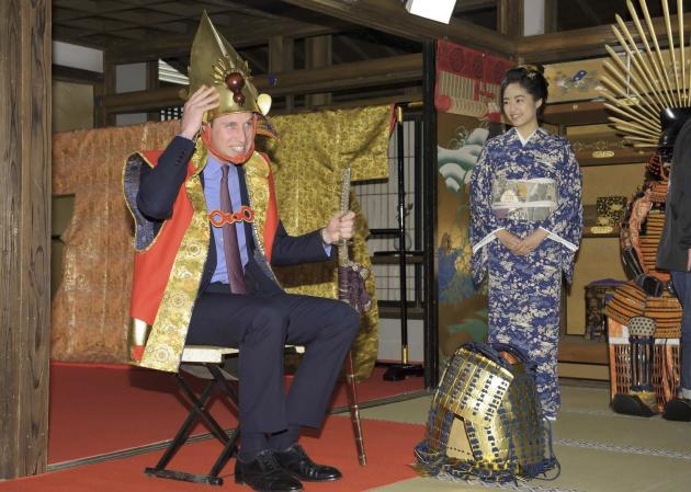 Handout photo shows Britain's Prince William trying on a samurai costume as Japanese actress Inoue looks on, during his visit a Taiga historical drama studio set at NHK in Tokyo