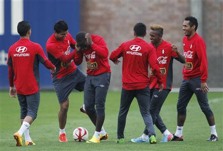 Peru's national soccer players joke around during a training session in Lima