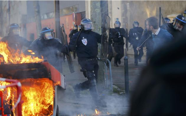 French riot police charge a protester during clashes at a demonstration to mark the anniversary of a march in 2014 which ended in violence, in Nantes