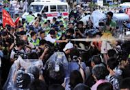 A policeman (centre left) fires pepper spray towards Hong Kong demonstrators calling on the Chinese government June 30 to investigate the death of dissident Li Wangyang. Activists said on Friday they rejected the official investigation which found that Li had died of suicide