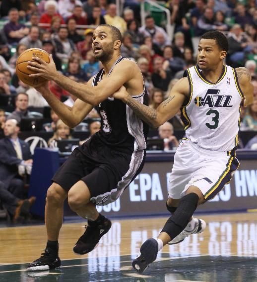 San Antonio Spurs' Tony Parker, left, drives the basket as Utah Jazz's Trey Burke (3) defends in the first half of an NBA basketball game on Saturday, Dec. 14, 2013, in Salt Lake City