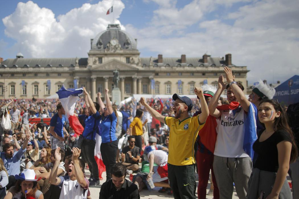 France fans react in the fan zone as they watch a EURO 2016 Round of 16 soccer match in Paris