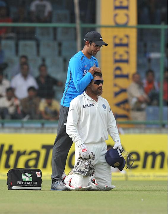 M S Dhoni of India being treated by physical therapist during the 4th test match of Border Gavaskar Trophy, at Ferozeshah Kotla Stadium in Delhi on March 22, 2013. P D Photo by Asish Maitra