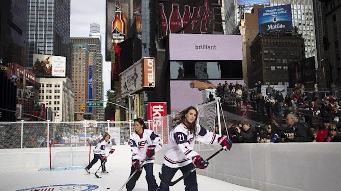 "Ice hockey competitors Hilary Knight, right, Julie Chu, center, and Meghan Duggan, left, skate on a plastic ""ice"" rink erected in Times Square during the U.S. Olympic Committee's event marking 100 days until the Sochi Games, Tuesday, Oct. 29, 2013, in New York"
