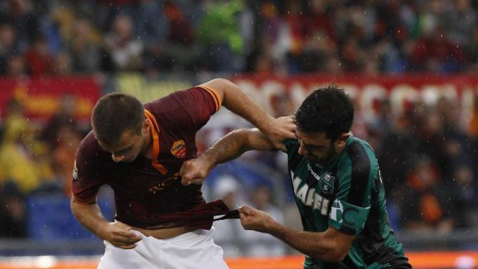AS Roma midfielder Kevin Strootman, of the Netherlands, is challenged by Sassuolo midfielder Francesco Magnanelli, right, during a Serie A soccer match between AS Roma and Sassuolo at Rome's Olympic stadium, Sunday, Nov. 10, 2013