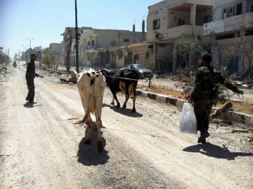 Syrian army soldiers walk with cows in a street in Qusayr in the central Homs province on June 6, 2013. Some 200 Russian Islamists who back North Caucasus insurgents are fighting in Syria for Al-Qaeda, the head of the Russian security service (FSB) said Thursday, Russian news agencies reported