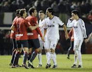 Real Madrid's Sami Khedira (2nd R) argues with Osasuna players during their Spanish La Liga match at the Reyno de Navarra stadium in Pamplona, on January 12, 2013. The match ended in a goalless draw