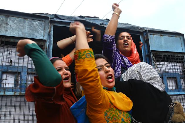 Kashmiri women employees of National Health Mission (NHM) shouts slogans from a police vehicle after being detained during a protest in Srinagar, Indian controlled Kashmir, Saturday, May 23, 2015. Pol