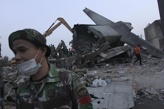 An Indonesian soldier stands near the tail section  of a military C-130 transport plane which crashed yesterday into a residential area in Medan, North Sumatra, Indonesia