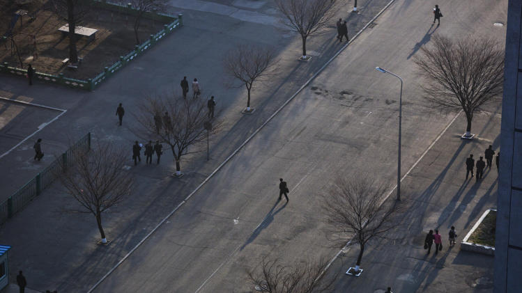 A North Korean commuter crosses a street in central Pyongyang on Wednesday, April 10, 2013. (AP Photo/David Guttenfelder)