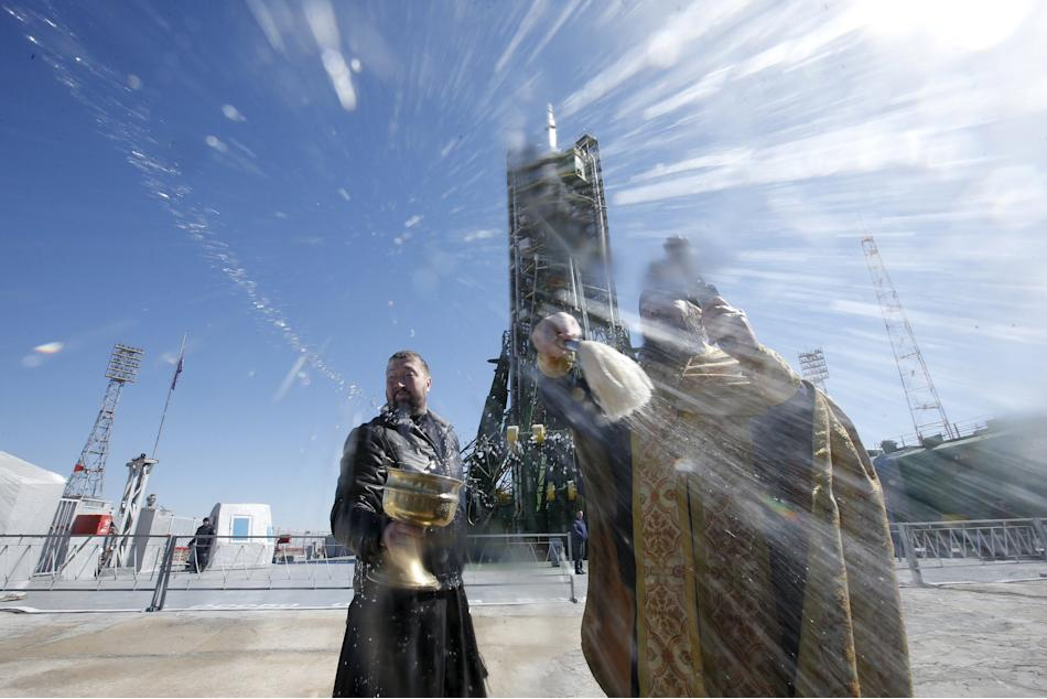 An Orthodox priest conducts a blessing in front of the Soyuz TMA-16M spacecraft set on the launch pad at Baikonur cosmodrome