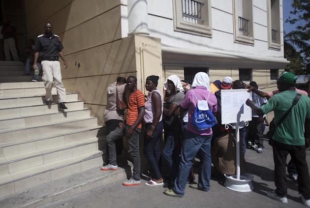 In this Sept. 4, 2014 photo, people line up outside Brazil's embassy to apply for visas in Petion-Ville, Haiti. While Haiti is picking itself up from the 7.0 earthquake that devastated its capital