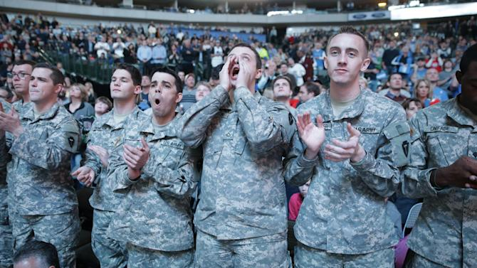 U.S. soldiers cheer from the front row before an NBA basketball game between the Milwaukee Bucks and Dallas Mavericks, Saturday, Dec. 14, 2013, in Dallas. Season ticket holders donated their front row seats to U.S. service members as part of the Mavericks 'Seats for Soldiers' program