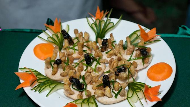 This undated photo provided by the United Nations Food and Agriculture Organization (FAO) shows a plate with insects during an insect cuisine competition at an unknown location in Laos. The U.N. has new weapons to fight hunger, boost nutrition and reduce pollution, and they might be crawling or flying near you right now: edible insects. The Food and Agriculture Organization on Monday, May 13, 2013, hailed the likes of grasshoppers, ants and other members of the insect world as an underutilized food for people, livestock and pets. A 200-page report, released at a news conference at the U.N. agency's Rome headquarters, says 2 billion people worldwide already supplement their diets with insects, which are high in protein and minerals, and have environmental benefits.  (AP Photo/Thomas Calame, FAO, ho)