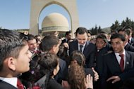 A picture from the Syrian Arab News Agency shows Syrian President Bashar al-Assad greeting children on Sunday as he attends a ceremony to commemorate Martyr's Day in Damascus' Jabal Kassioun area. Syria's authorities and the opposition traded accusations Sunday over who was behind blasts that rocked Damascus and Aleppo, on the eve of parliamentary polls designed to boost the regime's legitimacy