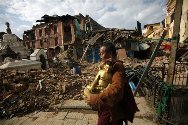 A Buddhist monk salvages a statue of a Buddhist deity from a monastery damaged by the earthquake in Kathmandu, Nepal. (AP Photo/Niranjan Shrestha)