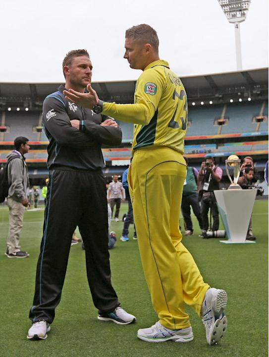 New Zealand's captain Brendon McCullum, center left, talks with Australia's captain Michael Clarke following a photo shoot with the Cricket World Cup trophy at the Melbourne Cricket Ground in