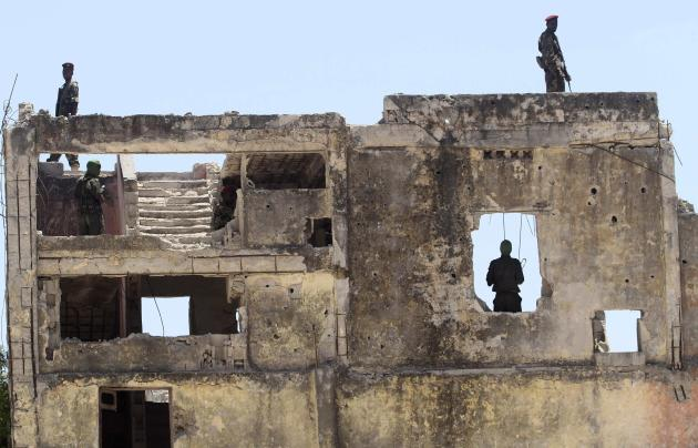 Members of Somalia's military forces stand guard at a ruined building during the arrival of Djibouti's President Guelleh at the Aden Abdulle International Airport in Somalia's capital Moga