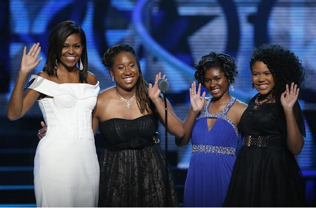 First Lady Michelle Obama, left, waves while standing on stage with Making A Difference award winners, from left, Kaya Thomas, Chental-Song Bembry and Gabrielle Jordan during a taping of the Black Gir