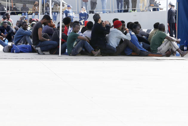 Migrants wait after disembarking from the Iceland Coast Guard vessel Tyr, at the Messina harbor, Sicily, southern Italy, Wednesday, May 6, 2015. This weekend saw a dramatic increase in rescues as smug