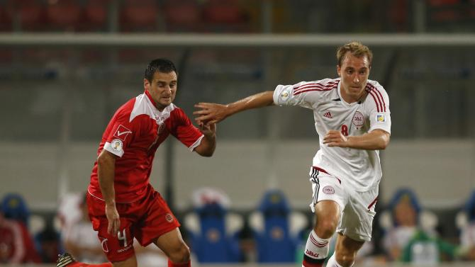 Denmark's Eriksen evades Malta's Sciberras during their 2014 World Cup qualifying soccer match at the National Stadium in Ta' Qali, outside Valletta