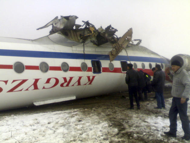 Emergency rescue personnel inspect an overturned Soviet-built Tupolev Tu-134 passenger jet after it crash-landed in deep fog in Osh, Kyrgyzstan, Wednesday, Dec. 28, 2011. Kyrgyzstan's Health Ministry said the Soviet-built Tu-134 jet was carrying 95 passengers and six crew when it crash-landed in deep fog Wednesday at the airport of the southern city of Osh. (AP Photo/AKI Press, Pool)