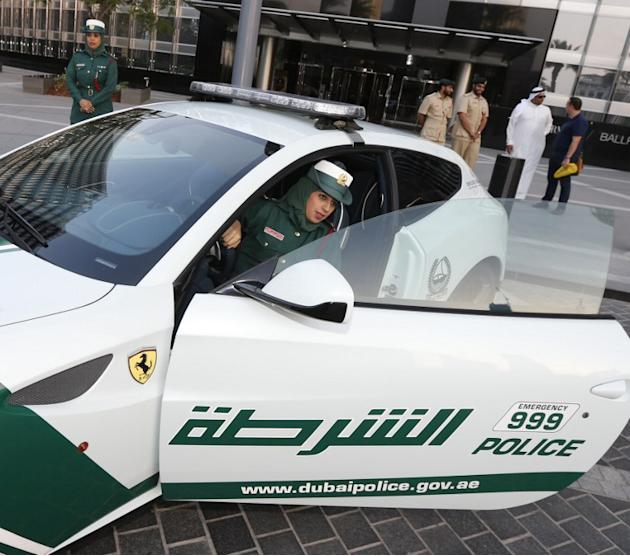 An Emirati female police officer poses sitting in a Ferrari police vehicle on April 25, 2013 in the Gulf emirate of Dubai. Dubai police showed off a new Ferrari they will use to patrol the city state,