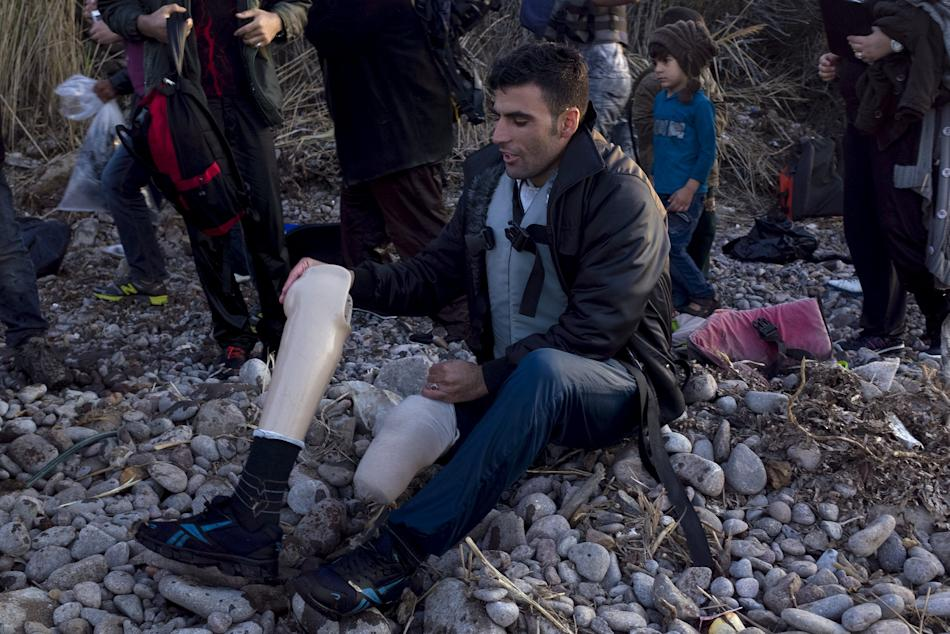 An Afghan refugee prepares to put on his prosthetic leg moments after arriving on an overcrowded dinghy on the Greek island of Lesbos, after crossing a part of the Aegean Sea from the Turkish coast