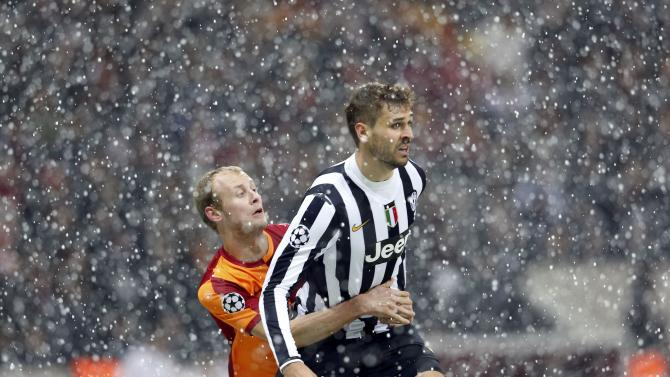 Kaya of Galatasaray and Llorente of Juventus collide as the snow continues to fall.