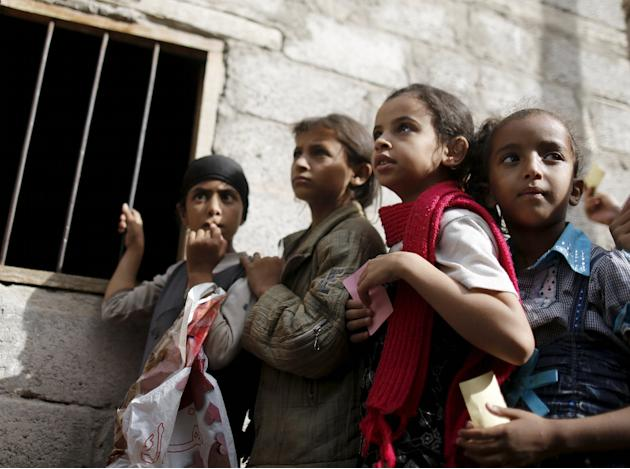 Girls wait for food rations outside a charity food assistance center in Yemen's capital Sanaa