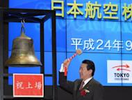 Japan Airlines Co. president Yoshiharu Ueki rings the bell during the company's relisting ceremony on the Tokyo Stock Exchange's First Section in Tokyo on September 19. The firm finished Friday at 3,680 yen, below the 3,790 yen it opened at on the Tokyo Stock Exchange Wednesday as it returned to the bourse less than three years after becoming one of Japan's biggest ever corporate failures