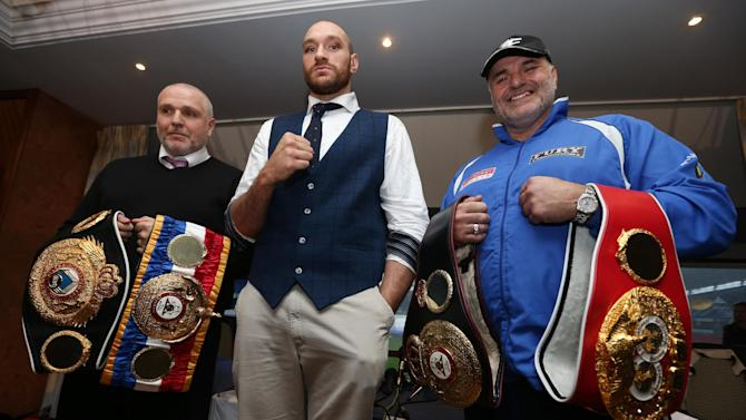 Tyson Fury poses with trainer Peter Fury and father John Fury after the press conference