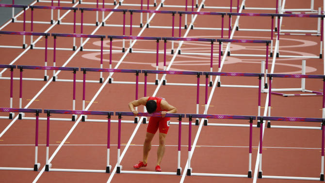 China's Liu Xiang kisses the last hurdle in his lane after his men's 110m hurdles round 1 heat at the London 2012 Olympic Games at the Olympic Stadium