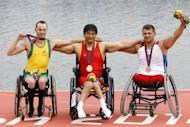 China's Cheng Huang (C) celebrates winning the gold medal in the AS men single sculls with silver medallist Australia'a Erik Horrie (L) and bronze medallist Russia's Aleksey Chuvashev during the London 2012 Paralympic Games