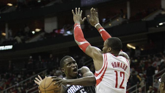 Orlando Magic shooting guard Victor Oladipo (5) drives to the basket on Houston Rockets power forward Dwight Howard (12) during the first quarter of an NBA basketball game on Sunday, Dec. 8, 2013, in Houston