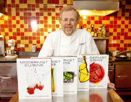 """FILE - In this March 23, 2011 file photo, Nathan Myhrvold, author of """"Modernist Cuisine: The Art and Science of Cooking,"""" as he poses with five books from the work at the Institute for Culinary Education in New York. On Friday, May 4, 2012, Myhrvold won a James Beard Award for Cookbook of the Year. (AP Photo/Stephen Chernin, File)"""