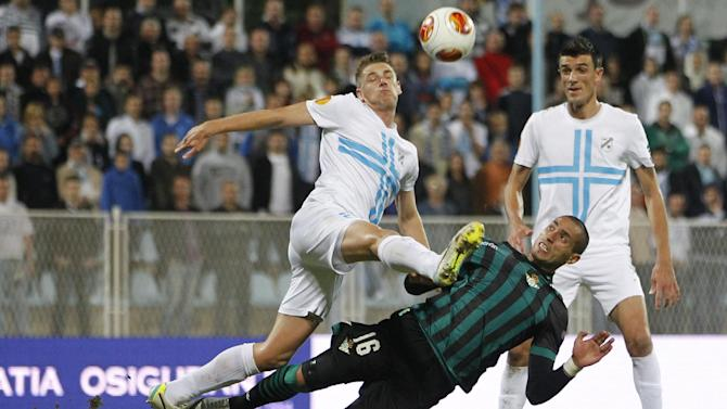 Betis' Brian Rodriguez, bottom, is challenged by Rijeka's Luka Maric, top left, during their group I Europa League first round second leg soccer match, at Kantrida stadium in Rijeka, Croatia, Thursday, Oct. 3, 2013