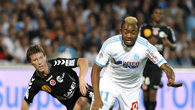 Marseille's Jordan Ayew, right, challenges for the ball with Stade de Reims' defender Franck Signorino during their League One soccer match, at the Velodrome Stadium, in Marseille, southern France, Saturday, Oct. 26, 2013
