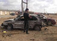 A man stands next to a car damaged after an explosion in the eastern city of Benghazi March 17, 2014. REUTERS/Esam Omran Al-Fetori