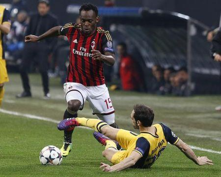 AC Milan's Michael Essien is challenged by Atletico Madrid's Juanfran during their Champions League round of 16 first leg soccer match at the San Siro stadium in Milan