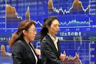 Pedestrians pass a share prices board in Tokyo. Asian markets mostly rose Thursday following upbeat earnings results in the region and the United States, while eurozone fears eased slightly on hopes over the funding of future bailouts