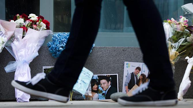A pedestrian walks past photographs and flowers placed at a memorial for Canadian actor Cory Monteith outside the Fairmont Pacific Rim Hotel in Vancouver, British Columbia on Monday, July 15, 2013. Monteith, 31, was found dead in his room at the hotel on Saturday, according to police, who have ruled out foul play. (AP Photo/The Canadian Press, Darryl Dyck)