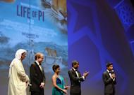 "DUBAI, UNITED ARAB EMIRATES - DECEMBER 09: Artistic Director of DIFF Masoud Amralla Al Ali, guest and actors Shravanthi Sainath, Adil Hussain and Suraj Sharma on stage ahead of the ""Life of PI"" Opening Gala during day one of the 9th Annual Dubai International Film Festival held at the Madinat Jumeriah Complex on December 9, 2012 in Dubai, United Arab Emirates. (Photo by Andrew H. Walker/Getty Images for DIFF)"