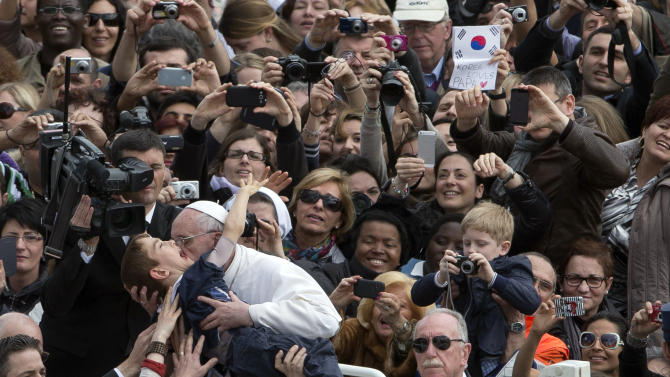 Pope Francis hugs a child after celebrating his first Easter Mass in St. Peter's Square at the Vatican, Sunday, March 31, 2013. Pope Francis celebrated his first Easter Sunday Mass as pontiff in St. Peter's Square, packed by joyous pilgrims, tourists and Romans and bedecked by spring flowers.Wearing cream-colored vestments, Francis strode onto the esplanade in front of St. Peter's Basilica and took his place at an altar set up under a white canopy. (AP Photo/Alessandra Tarantino)