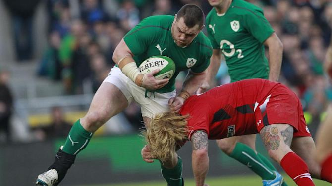 Ireland's Cian Healy, centre, is tackled by Wales' Richard Hibbard during their Six Nations Rugby Union international match at the Aviva Stadium, Dublin, Ireland, Saturday, Feb. 8, 2014