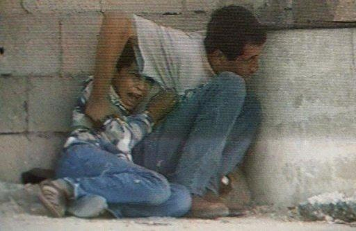 "TV grab from France 2 footage shows Jamal Al-Dura and his 12-year-old son hiding behind a barrel to protect themselves from Israeli-Palestinian crossfire on September 29, 2000. Israel has said that a France 2 television report seen worldwide on the death of a Palestinian child in 2000 was ""baseless"", following an analysis of the raw footage, drawing an angry reaction from the boy's father"