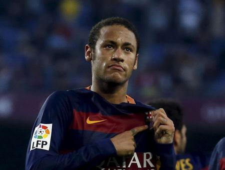 Barcelona's Neymar points FC Barcelona logo as he celebrates a goal against Villarreal during their Spanish first division soccer match at Camp Nou stadium in Barcelona