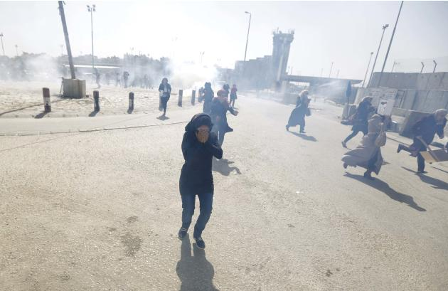 Palestinian women run wayfrom tear gas fired by Israeli  troops during clashes following a rally ahead of International Woman's Day, at Qalandiya checkpoint near the West Bank city of Ramallah