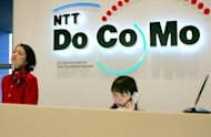 Enployees of NTT DoCoMo wait for customers at a counter of the company's headquarters in Tokyo. Japan's biggest telecom firm NTT Corp. said Friday that annual profit dipped 8.2 percent, but added that it expects a sharp rebound this year partly due to strong domestic smartphone sales